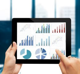 Closeup hand holding digital tablet show analyzing graph with conference room background