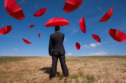 Man with Umbrella in a field with other umbrellas in ty