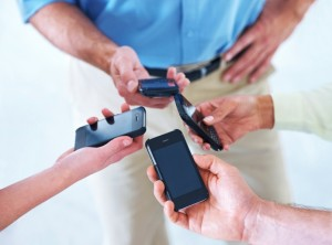 Cropped shot of four businesspeople putting their smartphones together