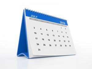 A monthly calendar with curled pages. July page is in focus. The calendar is blue in colour and standing on a white reflective background. Isolated on white. Clipping path is included.